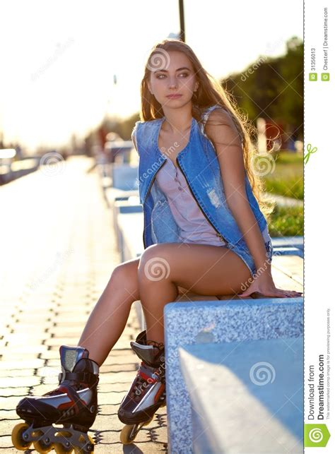 Roller Girl Wearing Jeans Sitting On Bench Stock Image