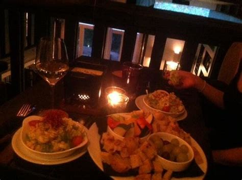 Cheese fondue with salad, grapes, vegetables and bread